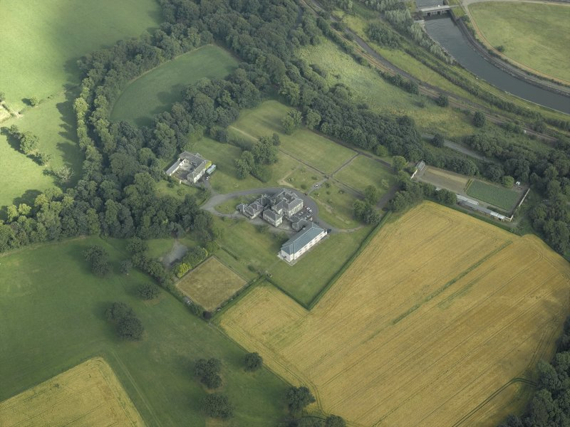 Oblique aerial view centred on the country house, formal garden and stables, taken from the SW.