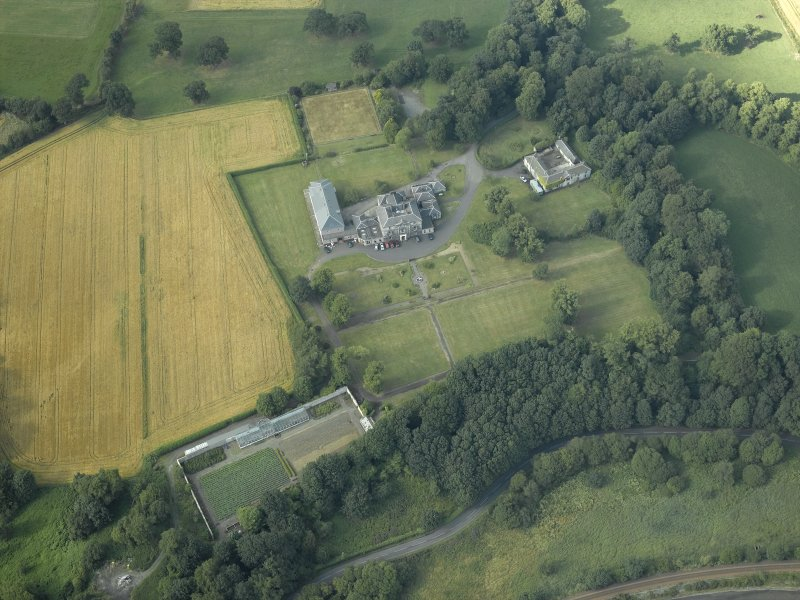 Oblique aerial view centred on the country house, formal garden and stables, taken from the S.
