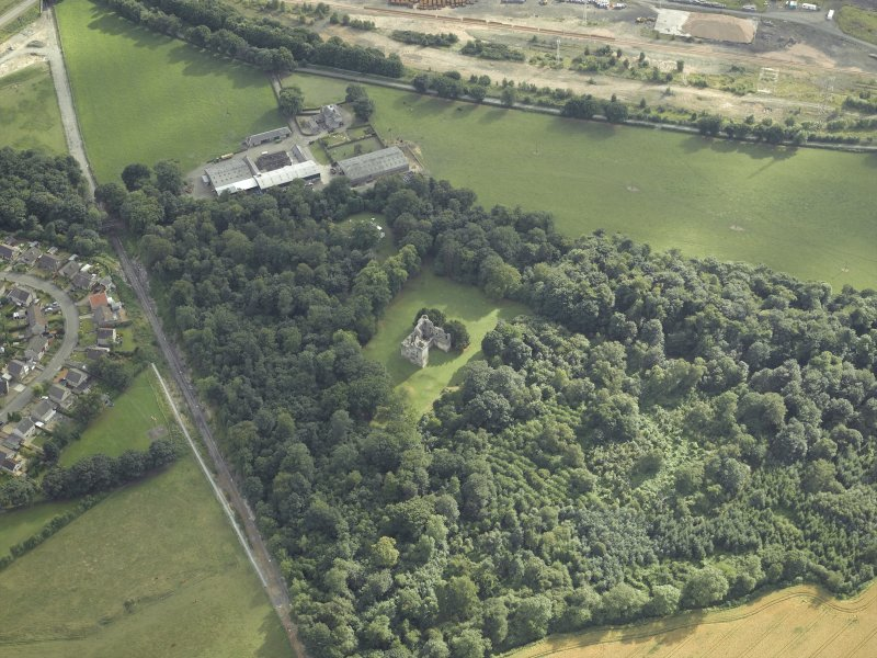 Oblique aerial view centred on the remains of the castle with the railway adjacent, taken from the NE.