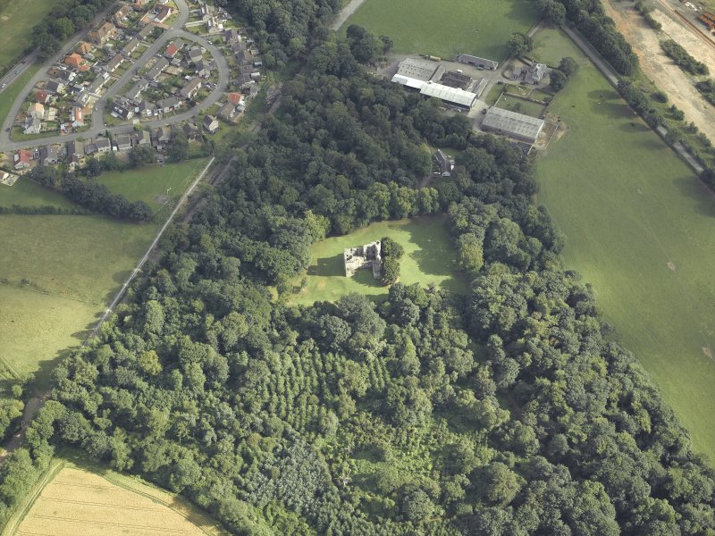 Oblique aerial view centred on the remains of the castle with the railway adjacent, taken from the NNW.