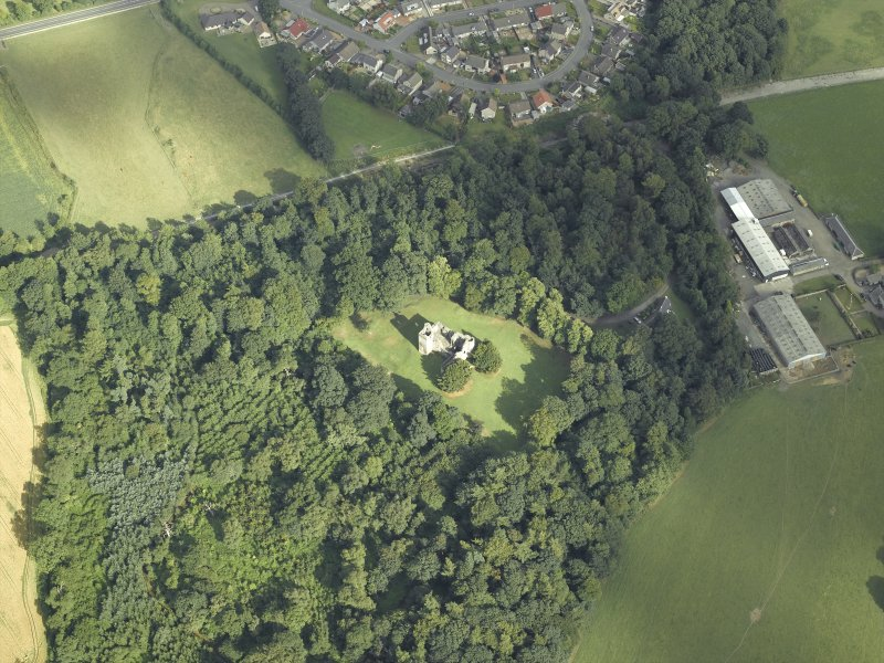 Oblique aerial view centred on the remains of the castle with the railway adjacent, taken from the WNW.