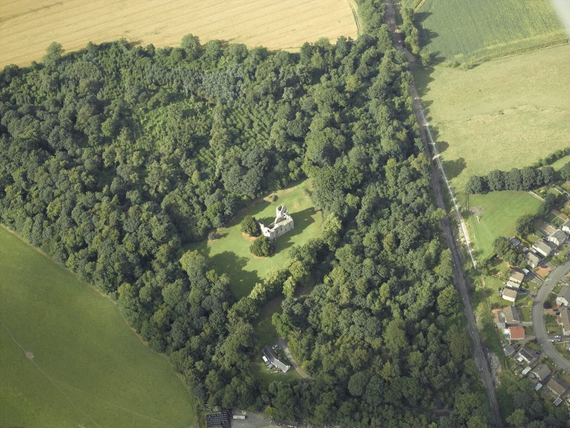 Oblique aerial view centred on the remains of the castle with the railway adjacent, taken from the SSW.