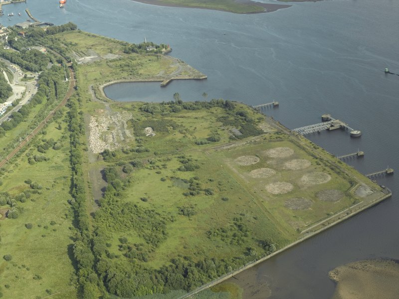 General oblique aerial view of the remains of the shipyard with the castle in the distance, taken from the NW.