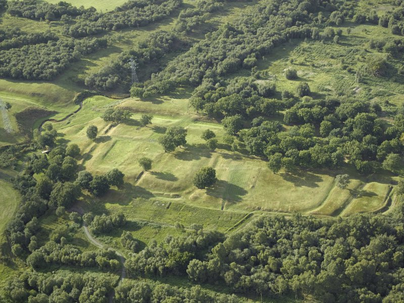 Oblique aerial view centred on the remains of the Roman fort and the course of the Antonine Wall, taken from the SE.