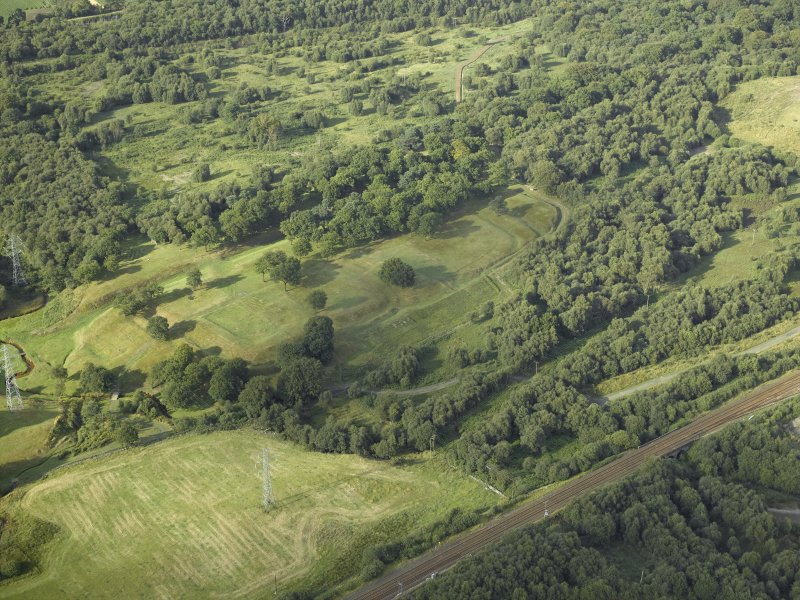 Oblique aerial view centred on the remains of the Roman fort and the course of the Antonine Wall, taken from the SW.