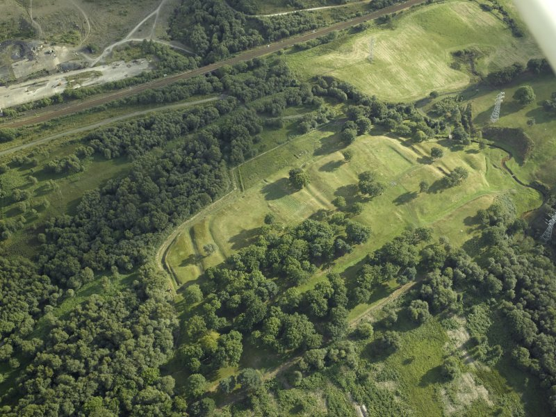 Oblique aerial view centred on the remains of the Roman fort and the course of the Antonine Wall, taken from the NNE.