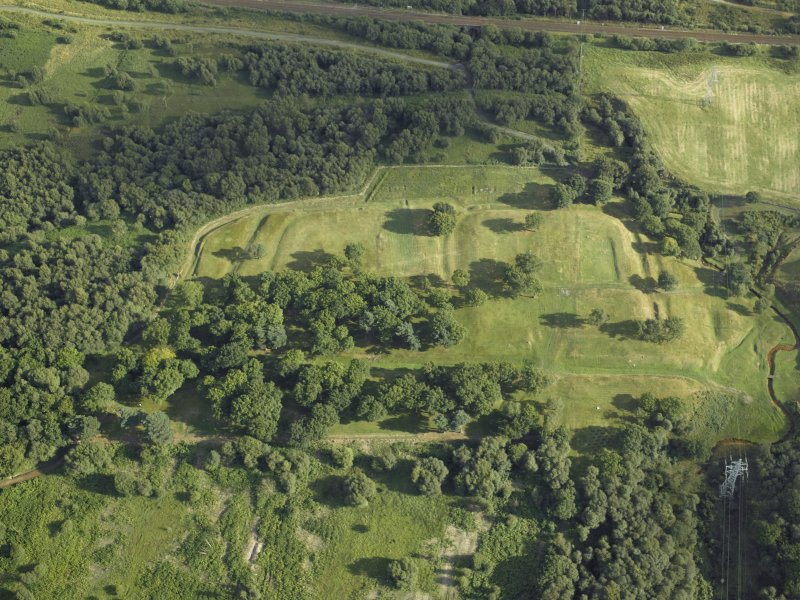 Oblique aerial view centred on the remains of the Roman fort and the course of the Antonine Wall, taken from the NW.
