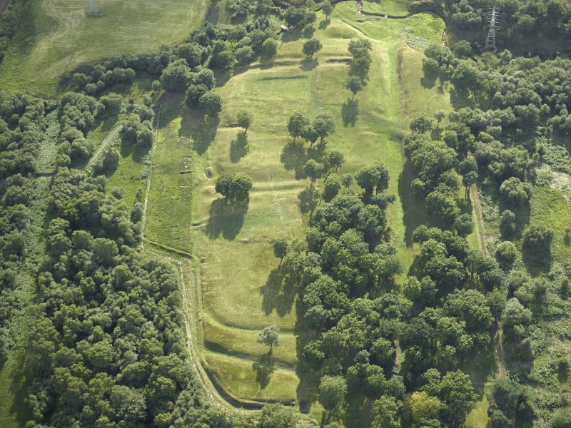 Oblique aerial view centred on the remains of the Roman fort and the course of the Antonine Wall, taken from the ENE.