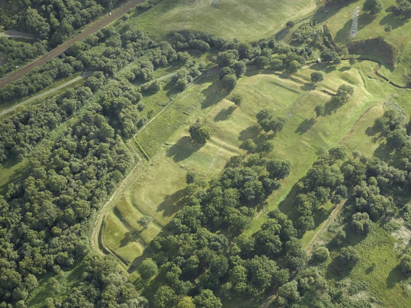 Oblique aerial view centred on the remains of the Roman fort and the course of the Antonine Wall, taken from the NE.