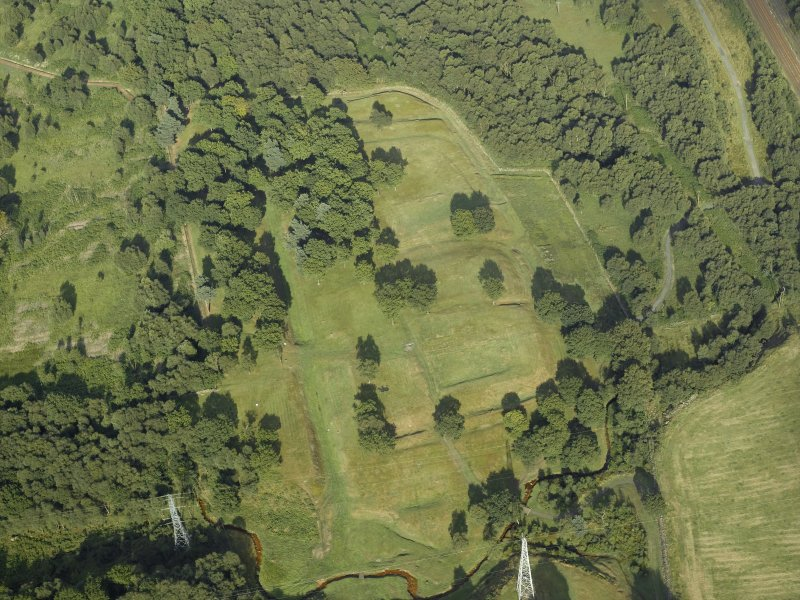 Oblique aerial view centred on the remains of the Roman fort and the course of the Antonine Wall, taken from the W.