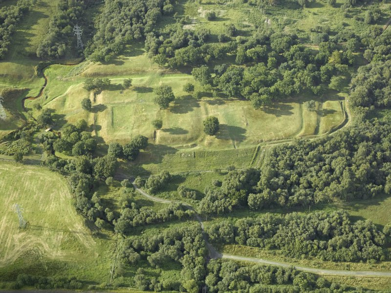 Oblique aerial view centred on the remains of Rough Castle Roman fort and the course of the Antonine Wall, taken from the S.