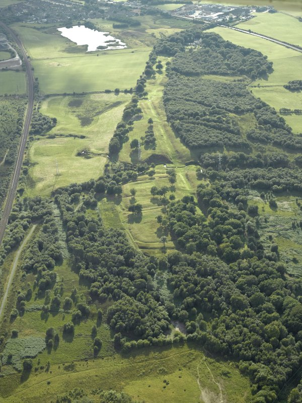 General oblique aerial view centred on the remains of the Roman fort and the course of the Antonine Wall, taken from the ENE.
