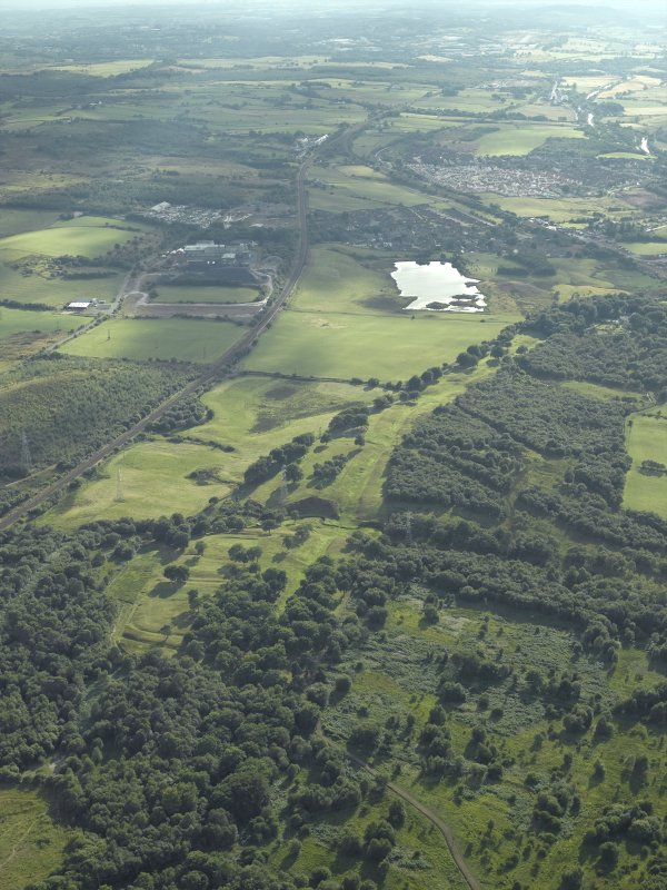 General oblique aerial view centred on the remains of the Roman fort and the course of the Antonine Wall, taken from the NE.