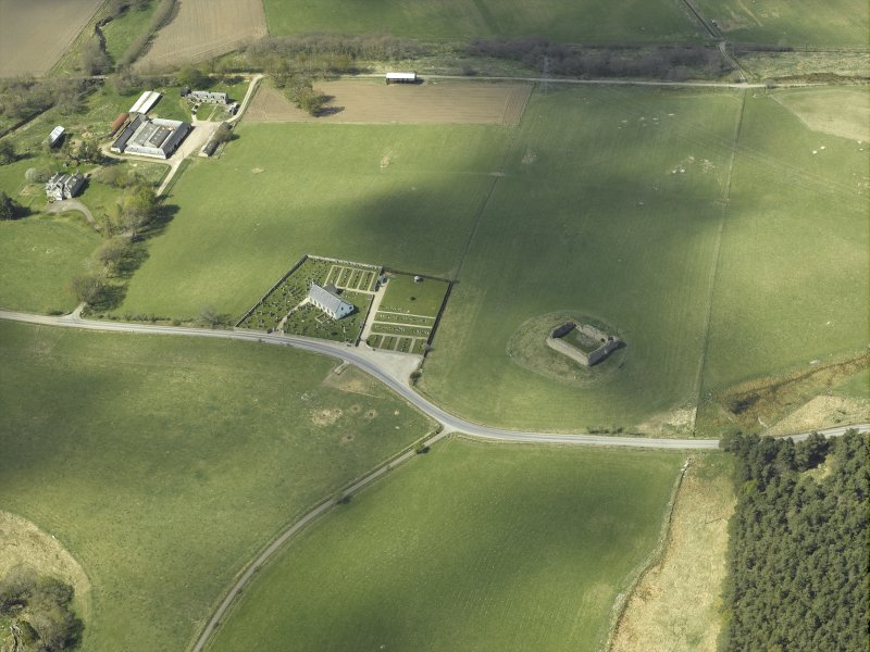 Oblique aerial view centred on the castle with the parish church adjacent, taken from the E.