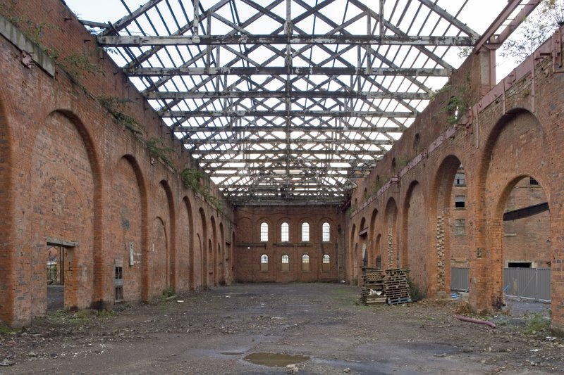 Interior. Heavy machine shop (former erecting shop) from E showing brick arcades with relieving arches (some pierced), king-post timber roof structure and N wall with oculi in parapet