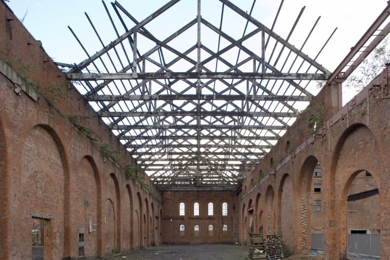 Interior. Heavy machine shop (former erecting shop) from E showing N brick aisle wall and extent of dismantling in advance of conversion
