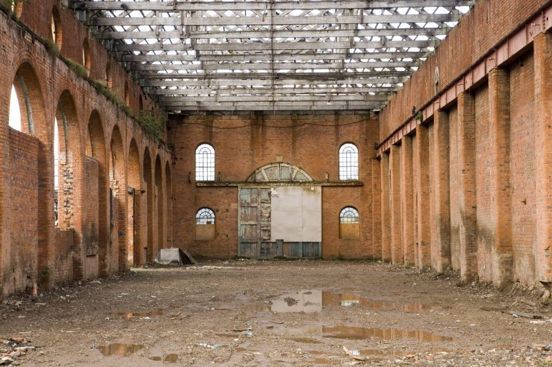Interior. View of light machine shop (former boiler shop) from E. Original wooden door and arched window arrangment visible