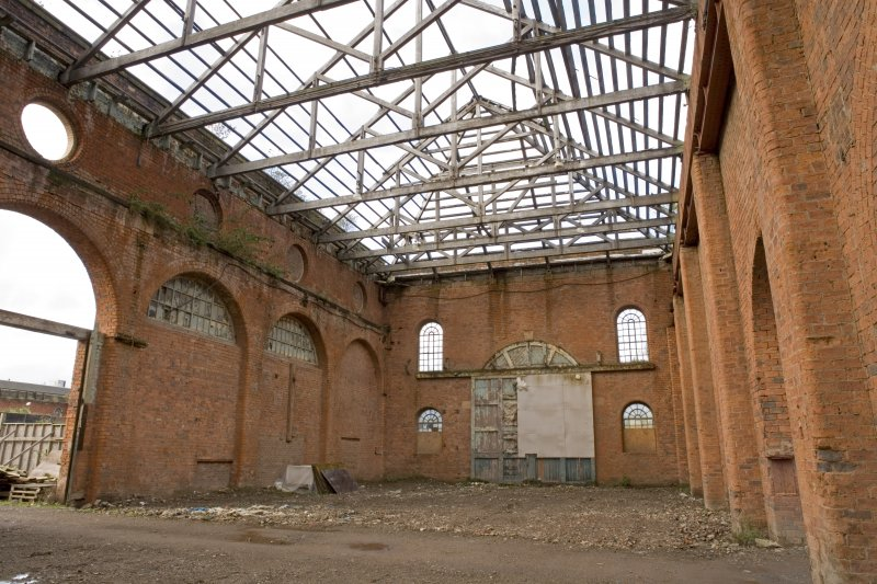Interior. View of light machine shop (former boiler shop) from NE. Original wooden door and arched window arrangment visible