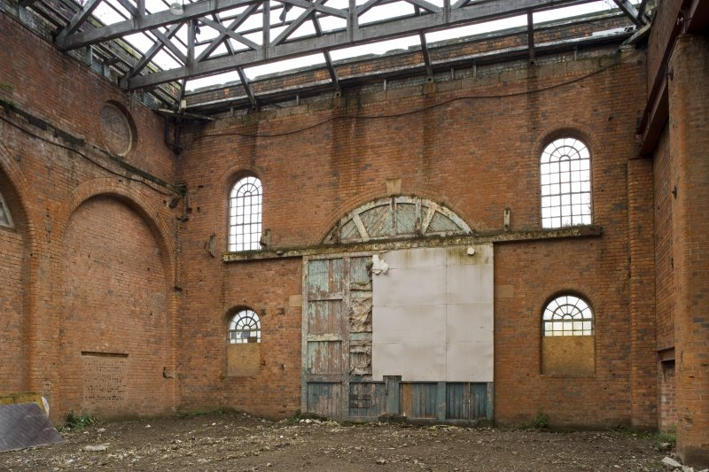 Interior. View of original wooden door to light machine shop (former boiler shop) and fenestration