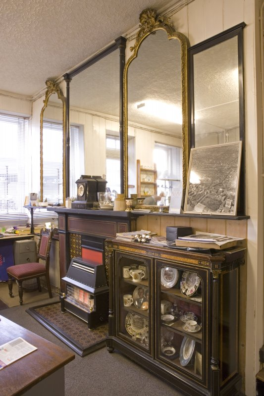 Interior. Ground floor. Back shop, detail office area. Fireplace and wall mirrors and late 19th century display cabinet.