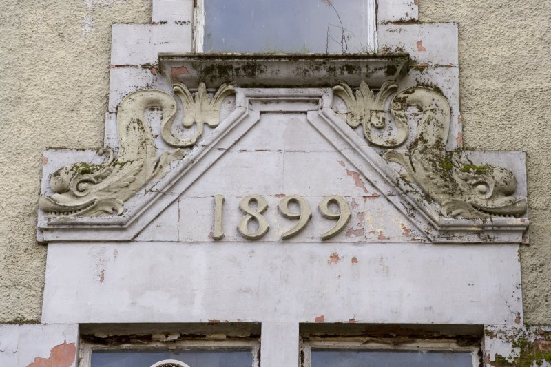 Main building. Detail of dated pediment above first floor bipartite window