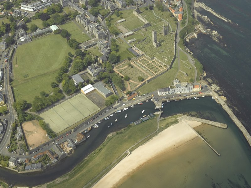 Oblique aerial view of St Andrews centred on the harbour with the cathedral and school adjacent, taken from the ESE.