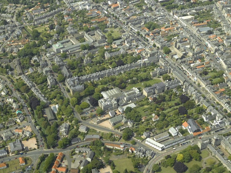 Oblique aerial view centred on the colleges, museum, libraries, church and town hall, taken from the SE.