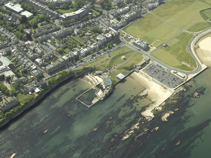 Oblique aerial view of St Andrews centred on the harbour and aquarium with the museum, shop, Royal and Ancient club house and monument adjacent, taken from the NE.