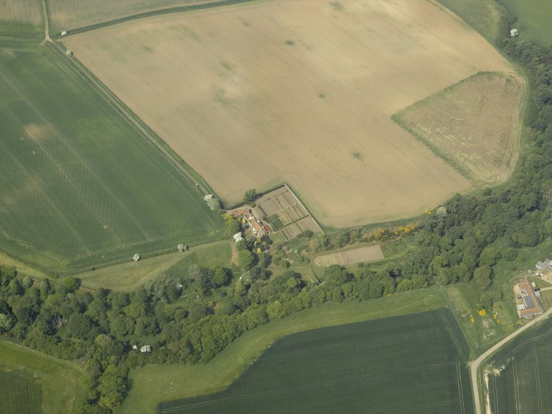 Oblique aerial view centred on the house with the road bridge adjacent, taken from the SE.