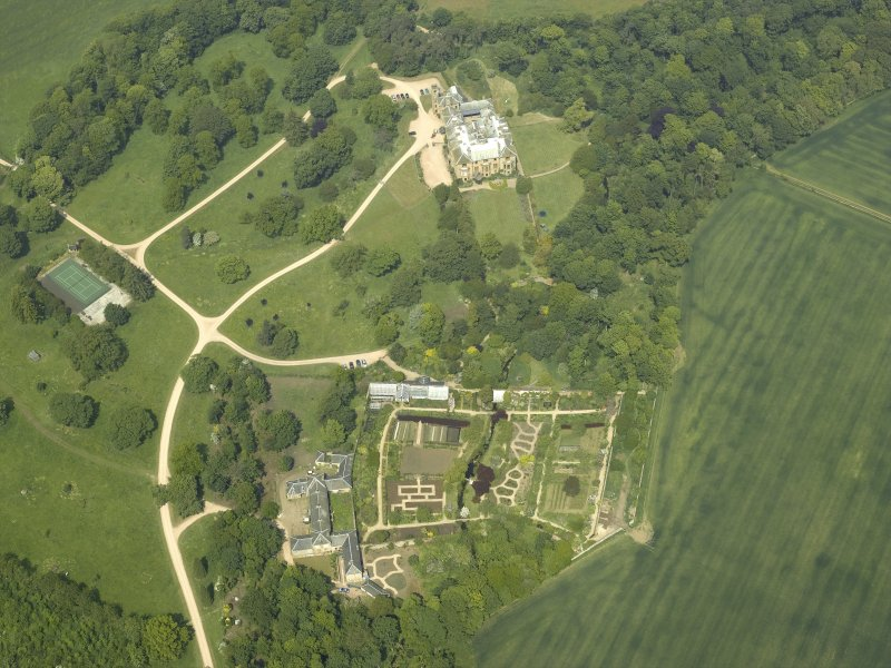 Oblique aerial view centred on the country house with the walled gardens and stables adjacent, taken from the S.