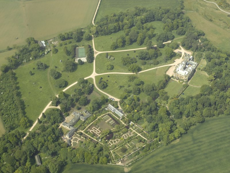 Oblique aerial view centred on the country house with the walled gardens and stables adjacent, taken from the ESE.