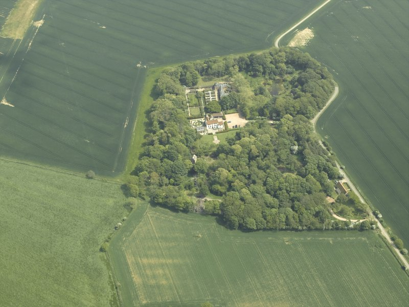 General oblique aerial view centred on the country house, stable block, dovecot and walled garden, taken from the W.