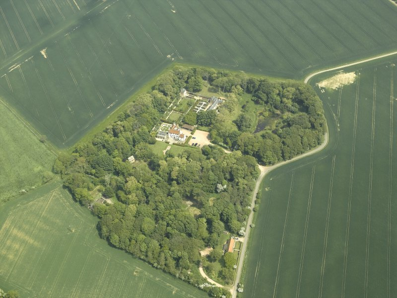 General oblique aerial view centred on the country house, stable block, dovecot and walled garden, taken from the SW.