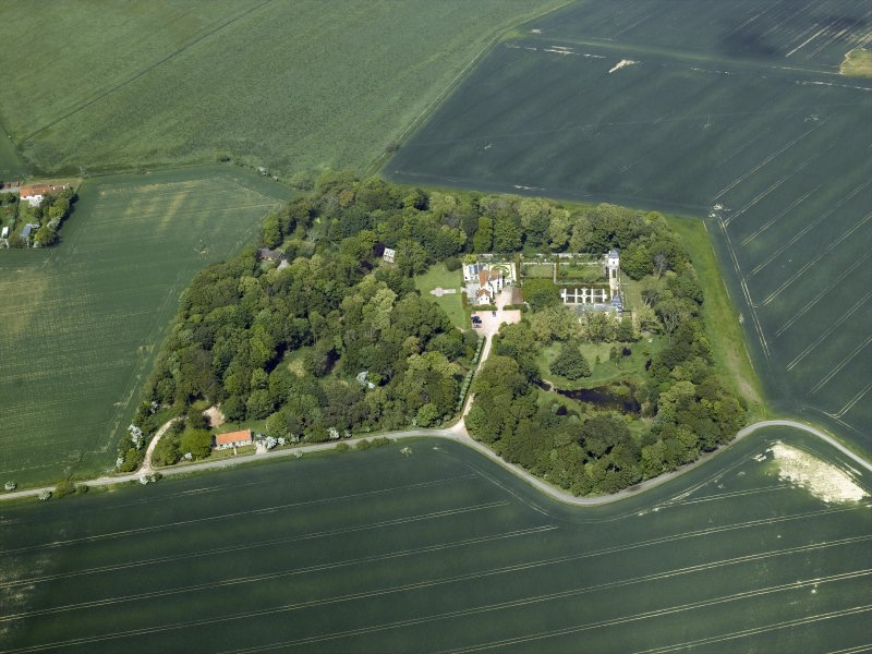 General oblique aerial view centred on the country house, stable block, dovecot and walled garden, taken from the S.