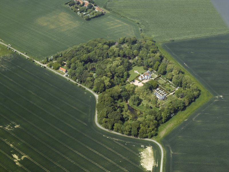 General oblique aerial view centred on the country house, stable block, dovecot and walled garden, taken from the SE.