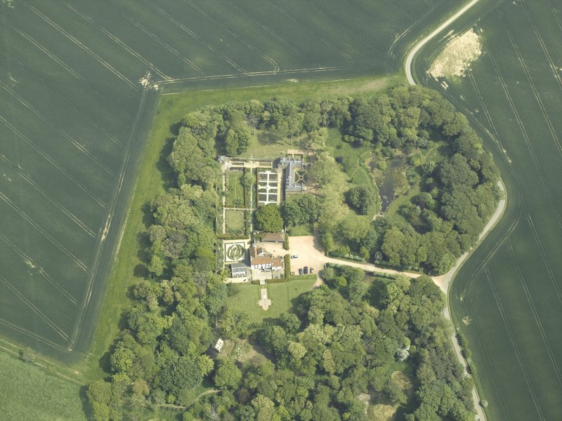 Oblique aerial view centred on the country house, stable block, dovecot and walled garden, taken from the W.