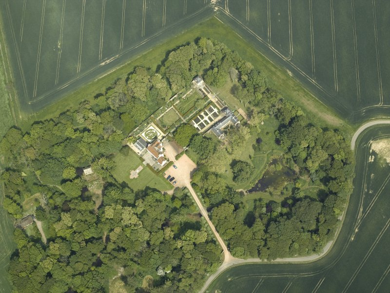 Oblique aerial view centred on the country house, stable block, dovecot and walled garden, taken from the SW.