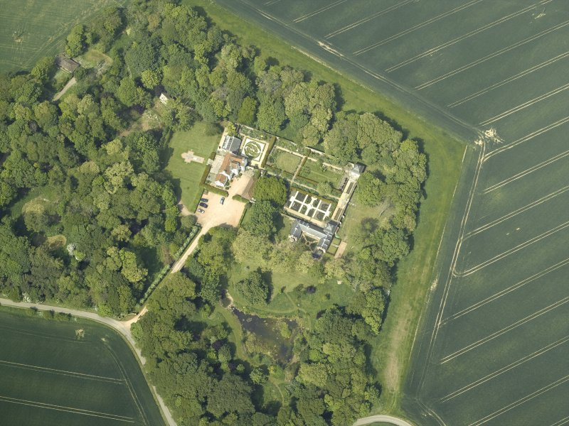 Oblique aerial view centred on the country house, stable block, dovecot and walled garden, taken from the SE.
