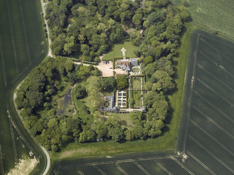 Oblique aerial view centred on the country house, stable block, dovecot and walled garden, taken from the E.