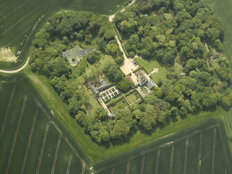 Oblique aerial view centred on the country house, stable block, dovecot and walled garden, taken from the NNE.