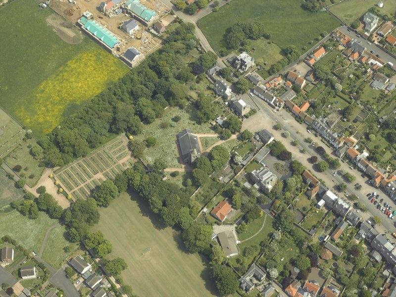 Oblique aerial view centred on the church, churchyard and burial ground with the hotel adjacent, taken from the WSW.