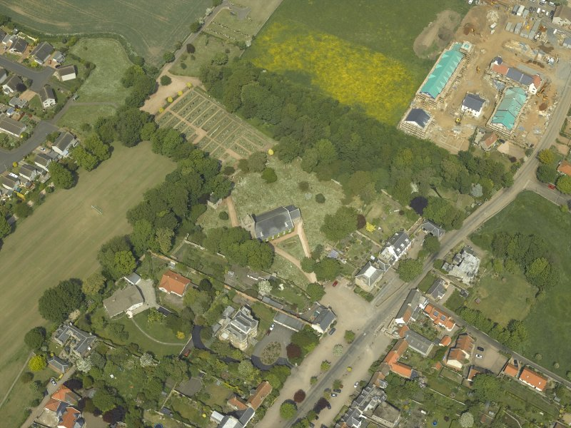 Oblique aerial view centred on the church, churchyard and burial ground with the hotel adjacent, taken from the S.