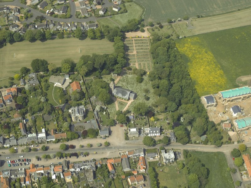Oblique aerial view centred on the church, churchyard and burial ground with the hotel adjacent, taken from the SE.