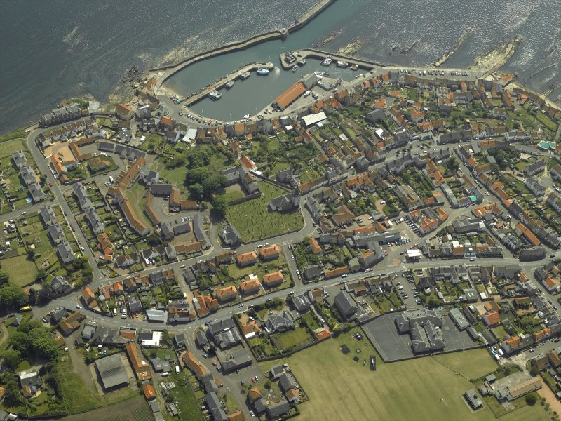 Oblique aerial view of the village centred on the priory, church, tollbooth and burial ground with the harbour adjacent, taken from the NNW.