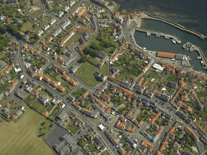 Oblique aerial view of the village centred on the priory, church, tollbooth and burial ground with the harbour adjacent, taken from the NW.