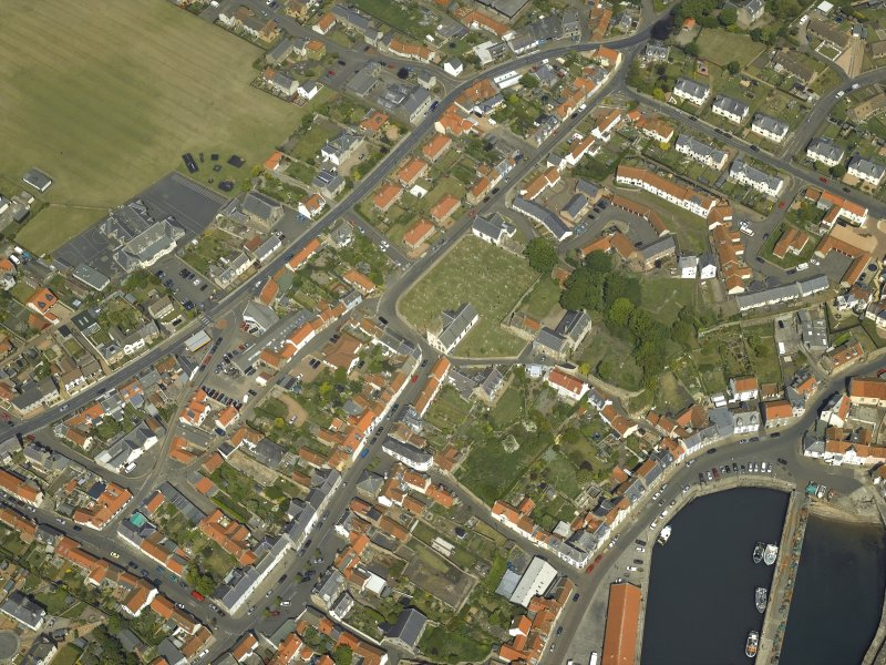 Oblique aerial view of the village centred on the priory, church, tollbooth and burial ground, taken from the SW.