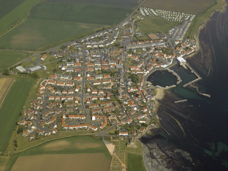 General oblique aerial view of the village centred on the harbour with the church and the burial-ground adjacent, taken from the SW.