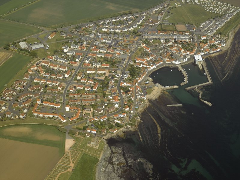 General oblique aerial view of the village centred on the harbour with the church and the burial-ground adjacent, taken from the SSW.