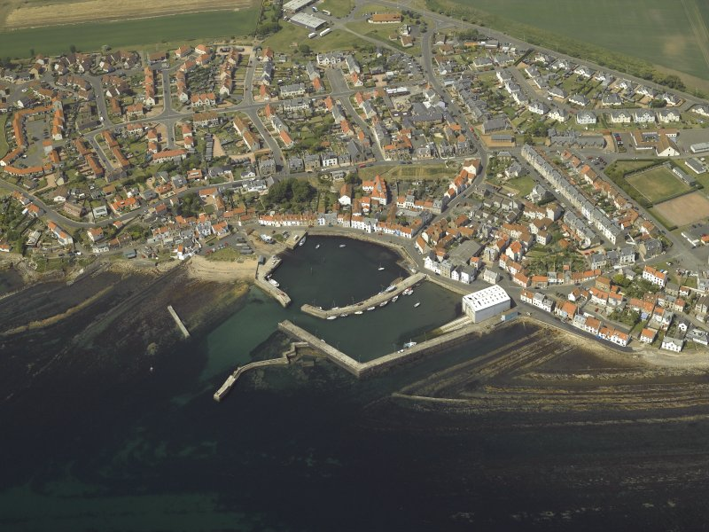Oblique aerial view of the village centred on the harbour, taken from the SE.