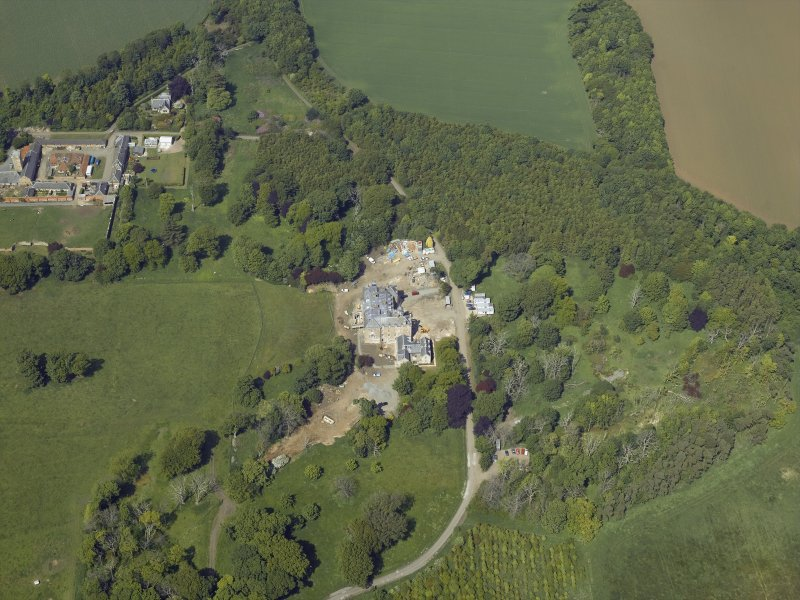 Oblique aerial view centred on the country house with the farmstead, sawmill and dovecot adjacent, taken from the S.